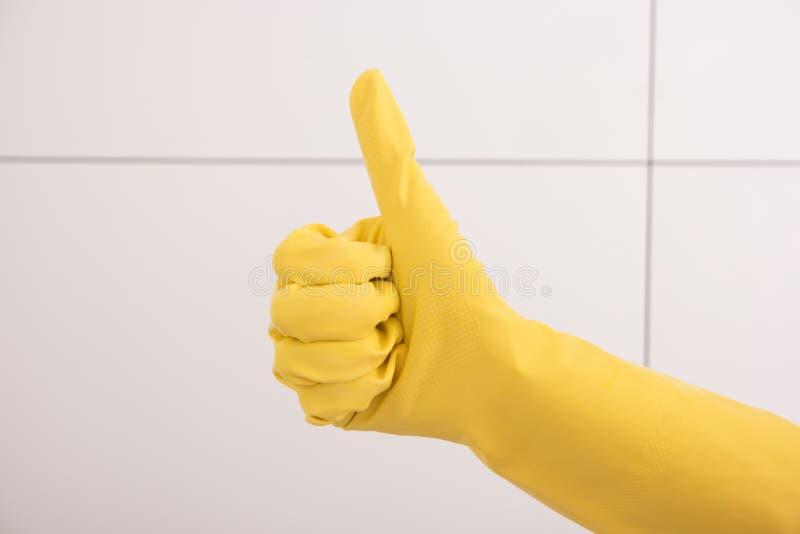 Tummar upp med en gul rubber handske royaltyfri bild