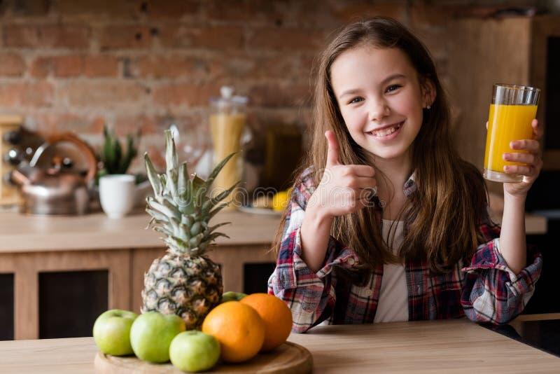 Tumme upp sund frukt för orange fruktsaft för ätaflicka royaltyfri bild