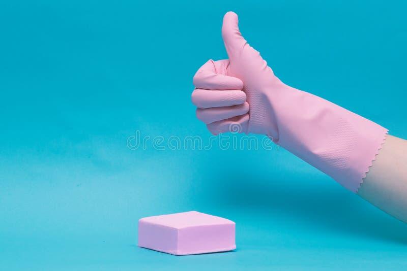 Tumme upp symbol i gummihandske rosa handske på blå bakgrund arkivfoton