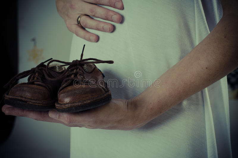 Tummy of pregnant woman with retro baby shoes stock photography