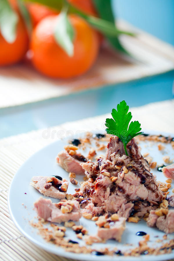 Tuna and Almonds with Vinegar Glaze. A plate of tuna in olive oil with toasted almonds and balsamic vinegar glaze stock image