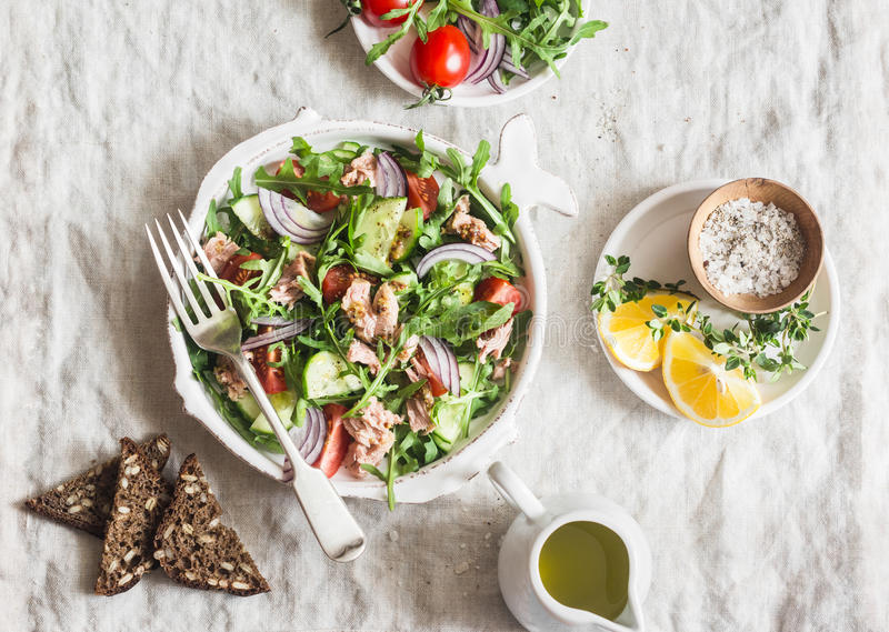 Tuna, arugula, tomato, cucumber salad with mustard dressing. Healthy diet food. Mediterranean style. On a light background stock images