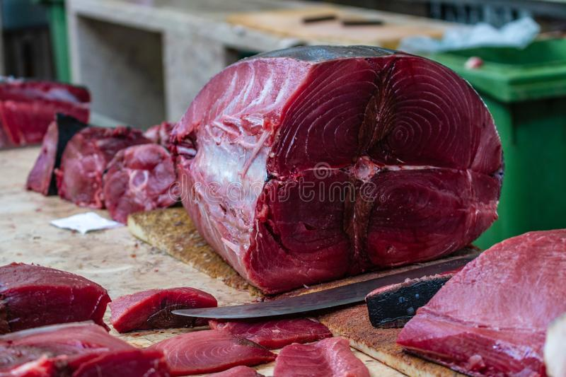A tuna being cleaned and cut at a fish market. royalty free stock image