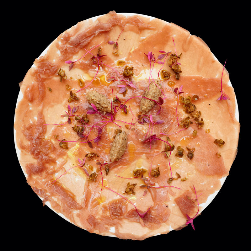 Tuna carpaccio with truffle paste and capers isolated on black royalty free stock image