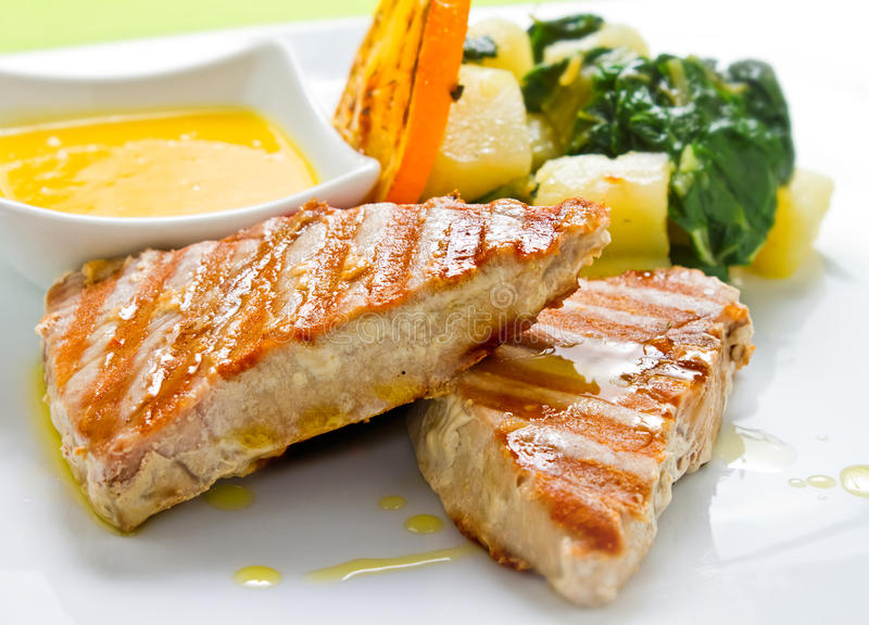 Tuna CloseUp. Grilled Tuna steaks served with boiled potato and lemon sauce, garnished with tomato and orange royalty free stock photos