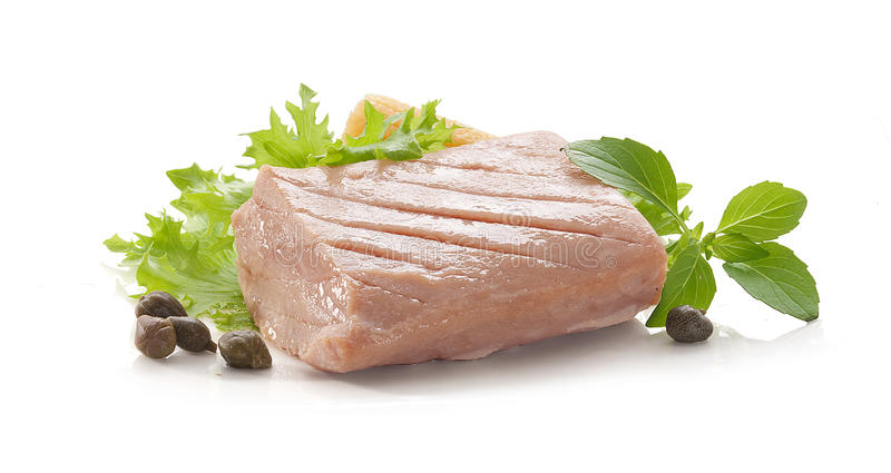 Tuna fillet. Piece of tuna fillet with fresh green lettuce, basil and mini corn stock photo