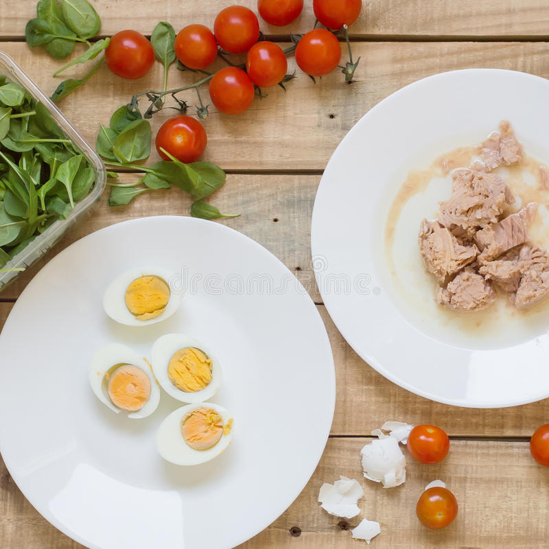 Tuna fish, bolied eggs, cherry tomatoes and baby spinach leaves. Tuna fish, boiled eggs, cherry tomatoes and baby spinach leaves on wooden background royalty free stock photography