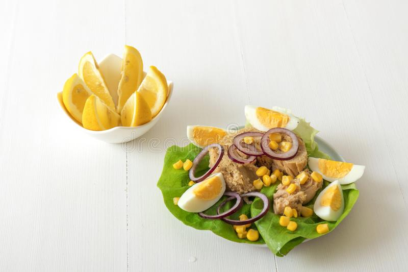 Tuna fish salad with sugar corn and eggs. Canned tuna with eggs, suggar corn, red onion rings on green lettuce leaf, slice of lemon in pocelain bowl..Tuna fish royalty free stock images