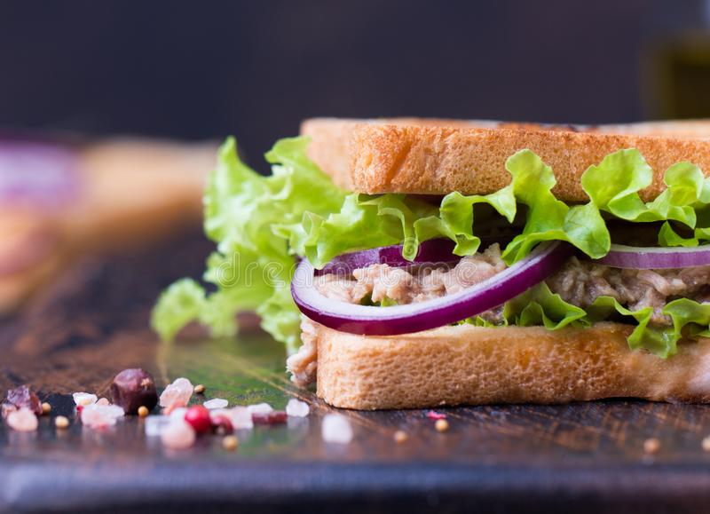Tuna fish sandwich with onion, lettuce and olive oil on a wooden board. royalty free stock image