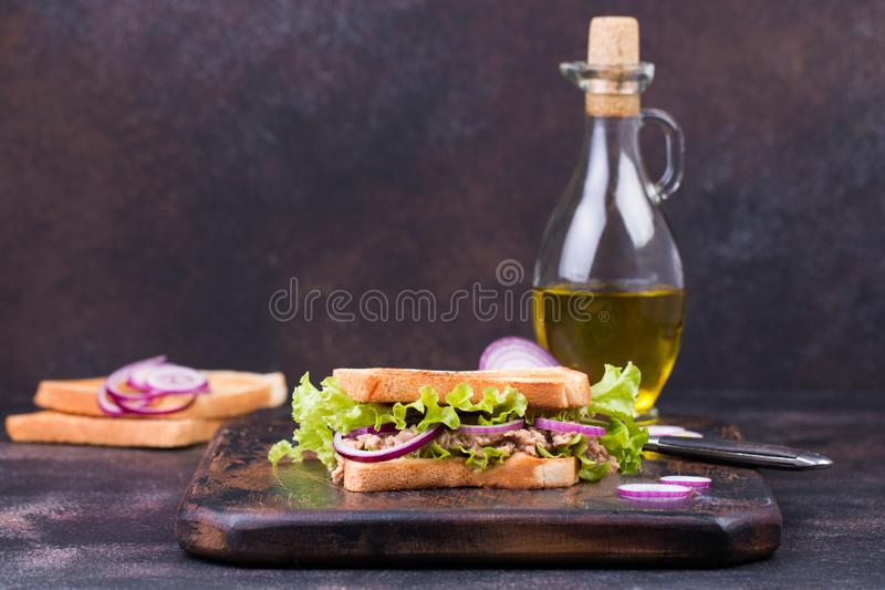 Tuna fish sandwich with onion, lettuce and olive oil on a wooden board. stock photos