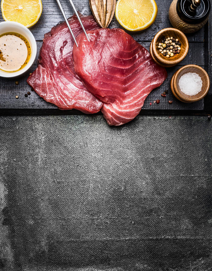 Tuna fish steaks with ingredients for grill or cooking on dark vintage background, top view stock image
