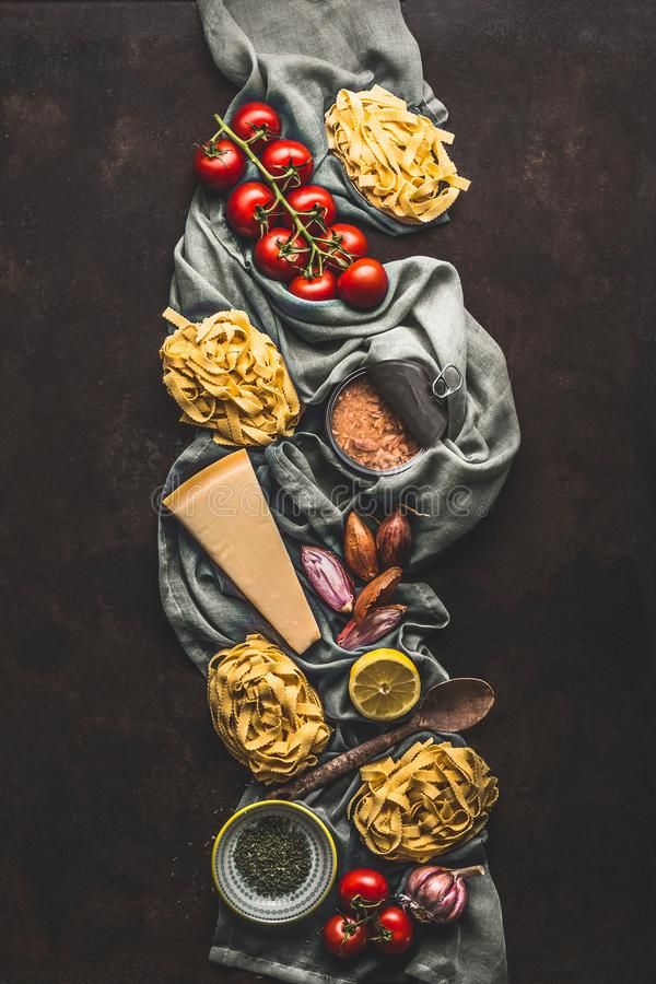 Tuna pasta cooking ingredients on dark rustic background, top view. Grocery products of Italian cuisine. Italian food. Caned tuna royalty free stock image