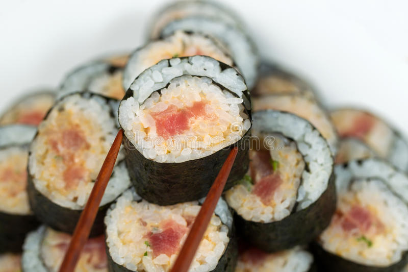 Tuna Roll picante que está sendo selecionada com hashis imagem de stock