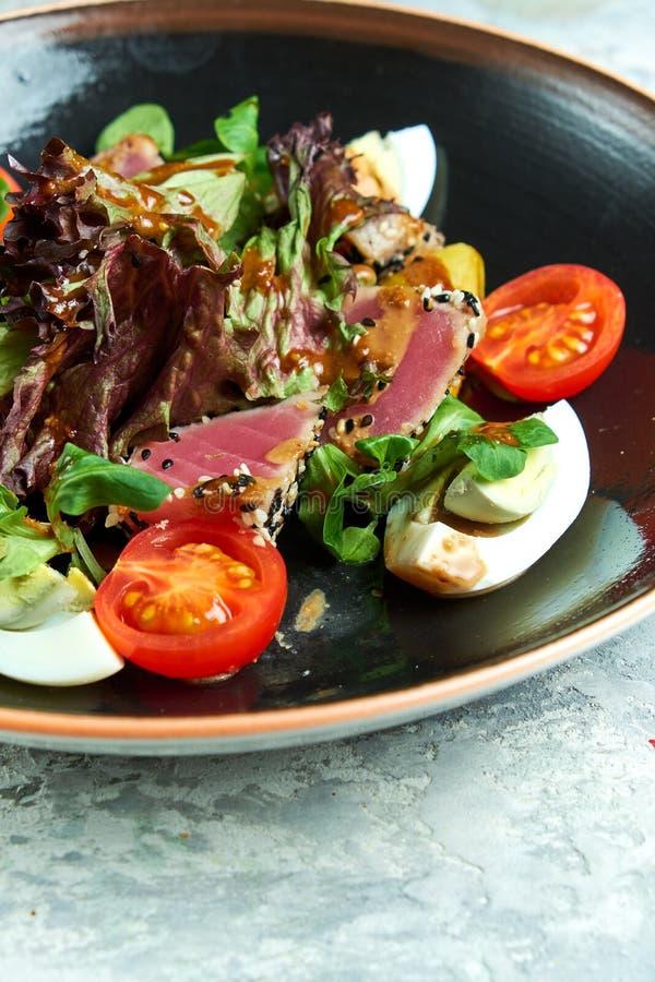 Tuna Salad caliente Platos de porci?n hermosos Fondo gris claro La cena de boda con la carne del rodillo fum? y los tomates fotografía de archivo