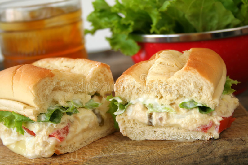 Tuna Salad Sandwich. Fresh tuna salad sandwich on a hoagie roll with ice tea and a bowl of lettuce in the background stock photo
