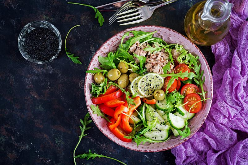 Tuna salad with tomatoes, olives, cucumber, sweet pepper and arugula. On rustic background . Top view royalty free stock images