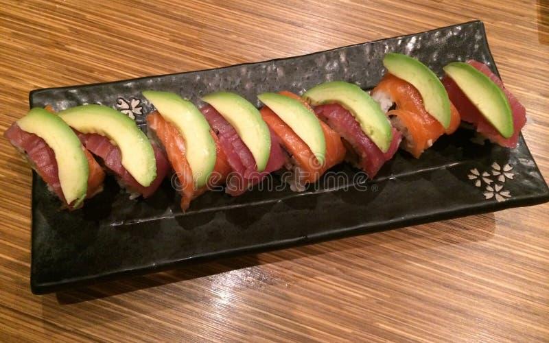 Tuna Salmon och avokadosushirulle i restaurang, regnbågesushirulle består av den nya lax-, tonfisk- och avokadoskivan, stylistmat arkivbilder