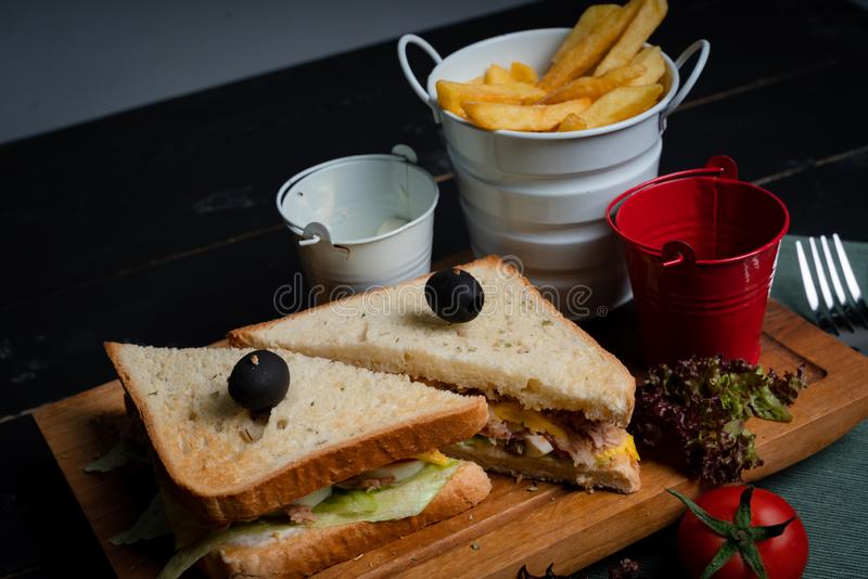 Tuna sandwich on a wooden tray with French fries. royalty free stock photo