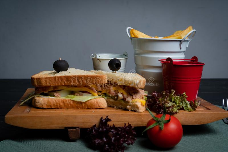 Tuna sandwich on a wooden tray with French fries. stock photo