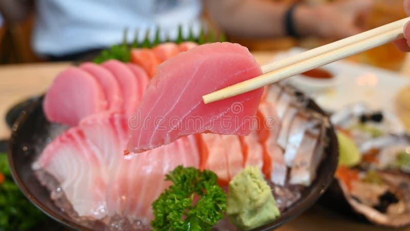 Tuna sashimi slice on chopsticks royalty free stock photography