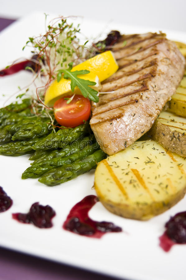 Tuna steak. Elegant restaurant table setting with tuna steak dish royalty free stock photo