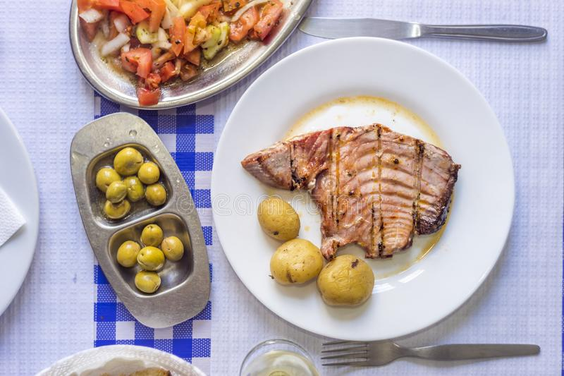 Tuna steak accompanied with potatoes, olives, tomato salad and w. Ine on white plate stock photos