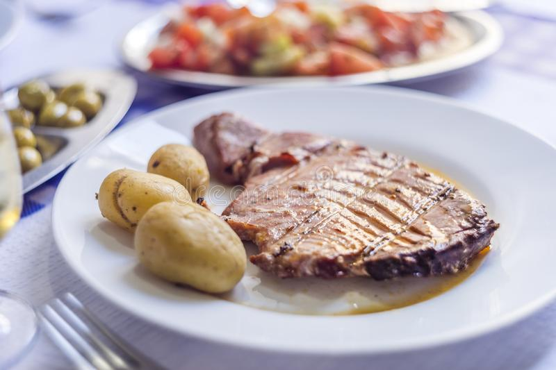 Tuna steak accompanied with potatoes, olives, tomato salad and w. Ine on white plate royalty free stock image