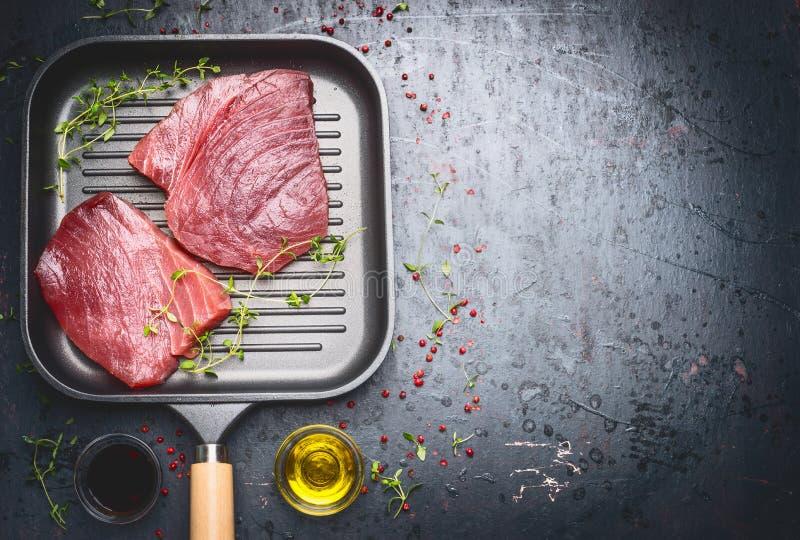 Tuna Steak cruda en sartén de la parrilla con las hierbas y el aceite en oscuridad envejeció el fondo del vintage, visión superio fotos de archivo
