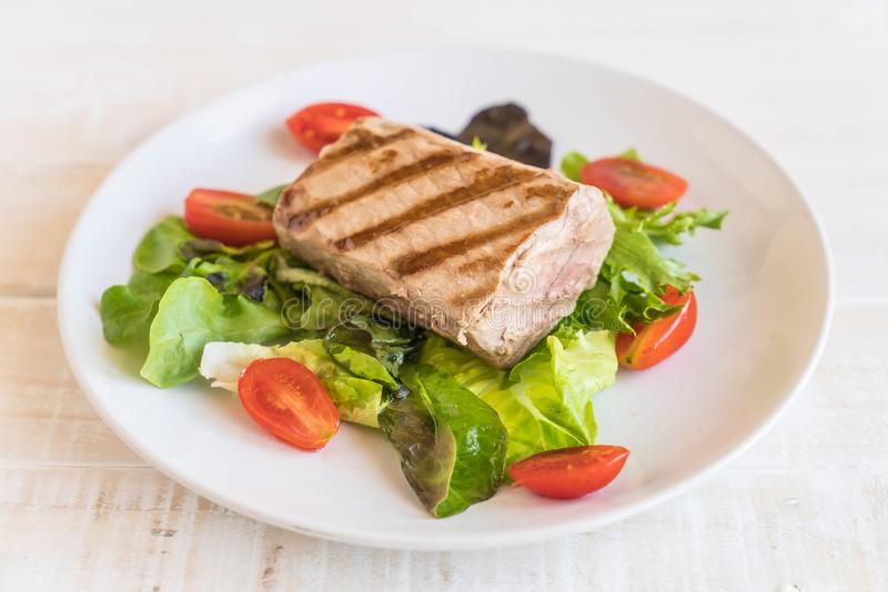 Tuna steak with salad. On wood table stock image