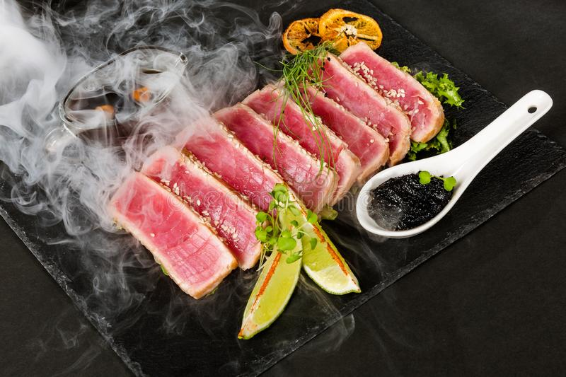 Tuna steak and smoke. Sliced tuna steak with lime and sesame in puffs of white smoke stock image