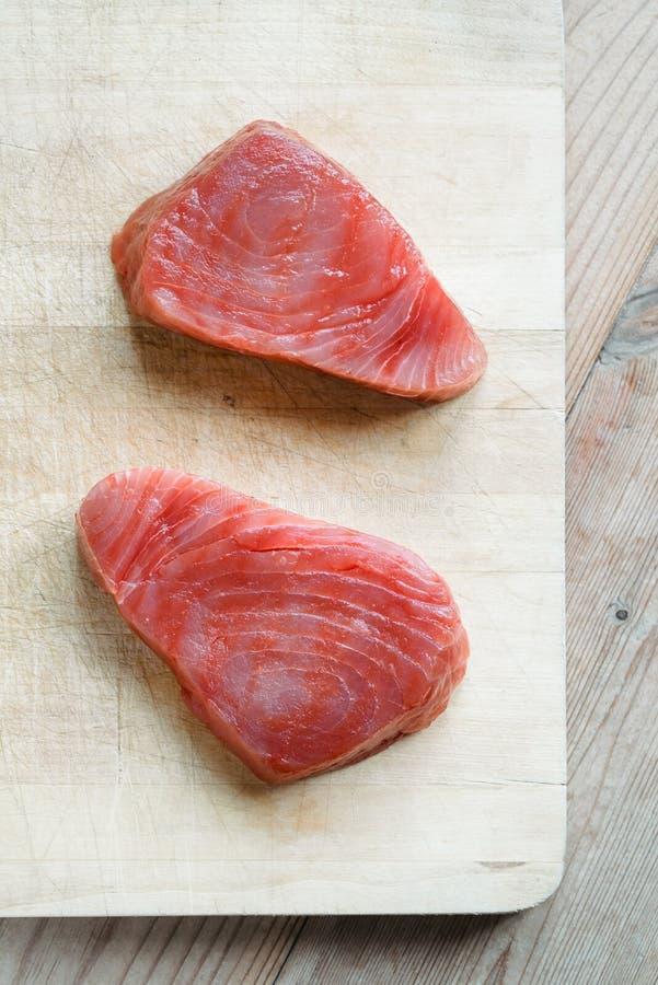 Tuna steaks. Raw tuna steaks on wooden cutting board royalty free stock photos