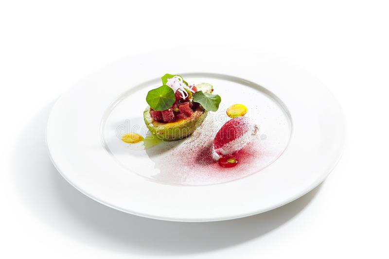 Tuna Tartar Made from Raw Fish Served in Avocado. With lime ice cream on white restaurant plate isolated. Exquisite serving yellowfin sashimi tatar in alligator stock image