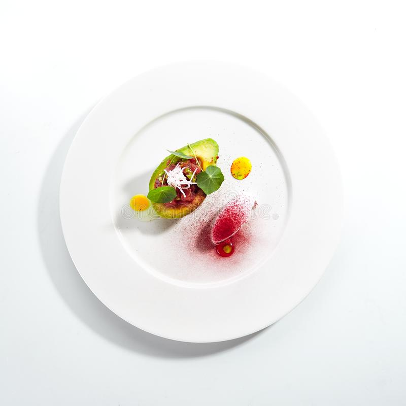 Tuna Tartar Made from Raw Fish Served in Avocado. With lime ice cream on white restaurant plate isolated. Exquisite serving yellowfin sashimi tatar in alligator stock images