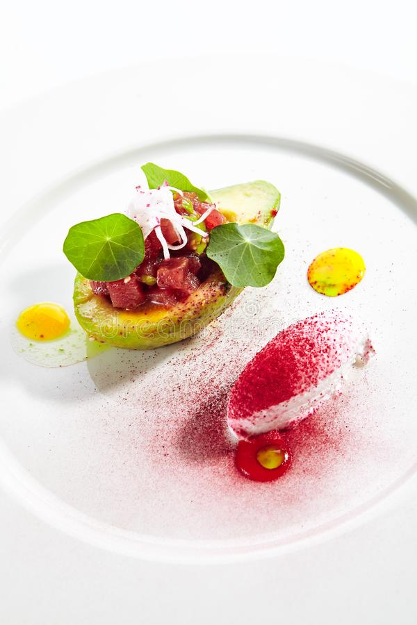 Tuna Tartar Made from Raw Fish Served in Avocado. With lime ice cream on white restaurant plate isolated. Exquisite serving yellowfin sashimi tatar in alligator royalty free stock photos