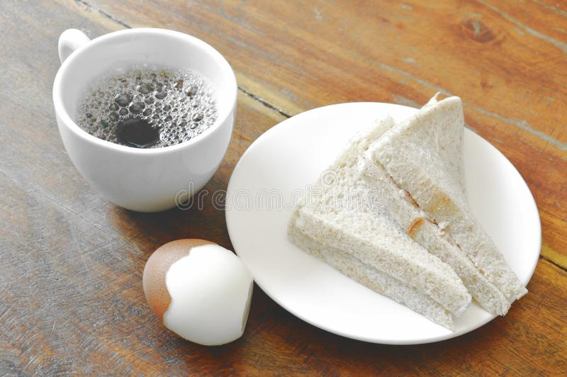 Tuna whole wheat sandwich on plate and boiled egg eat couple with black coffee cup stock photos