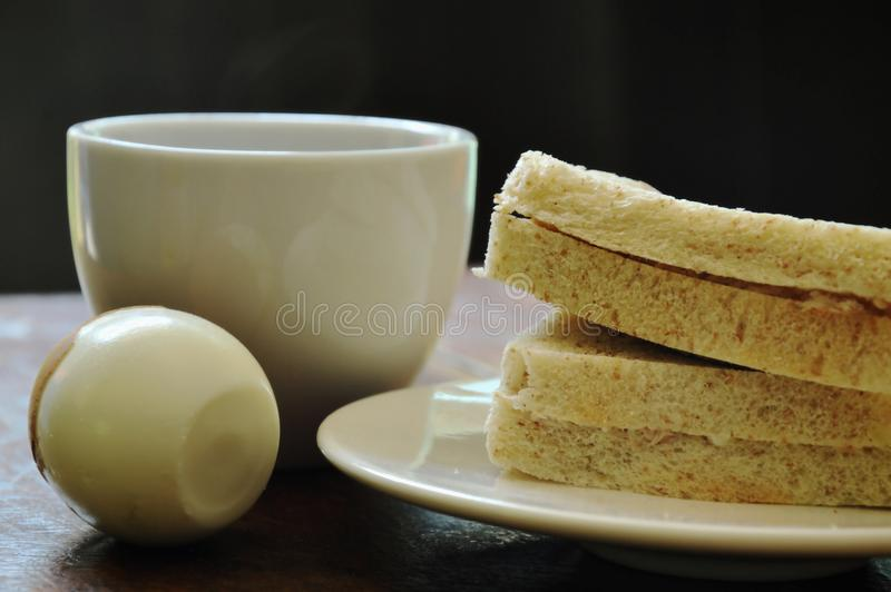 Tuna whole wheat sandwich on plate and boiled egg eat couple with black coffee cup stock image