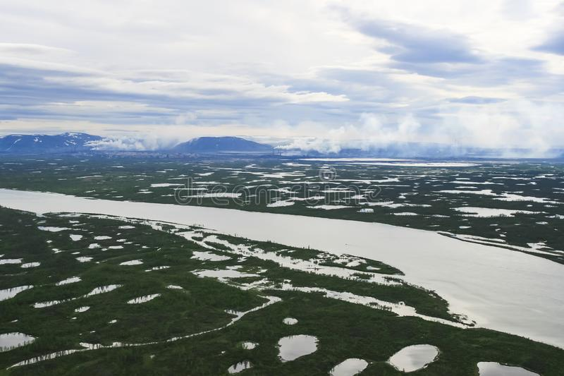 Tundra, lakes and rivers amid smoke and pipes stock photo