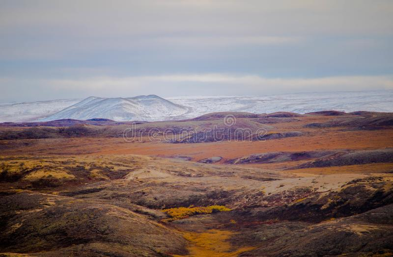 Tundra. The tundra near Paulutuk Northwest Territories Canada. Tundra in foreground and a snow capped mountain range in the background under a cloudy sky stock image