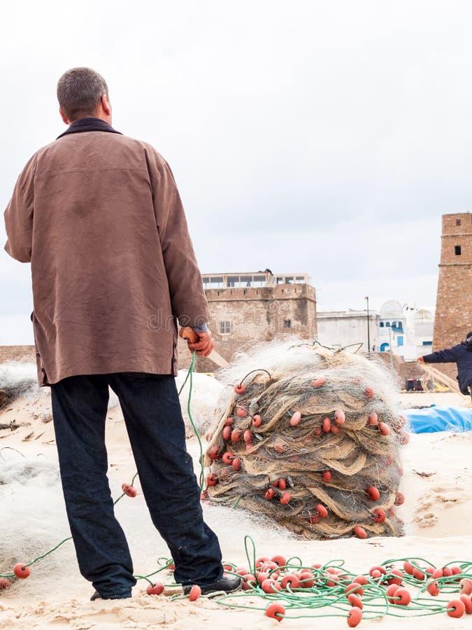Tunesië aan Hammamet-visser bereidt visnetten op het strand voor royalty-vrije stock foto's