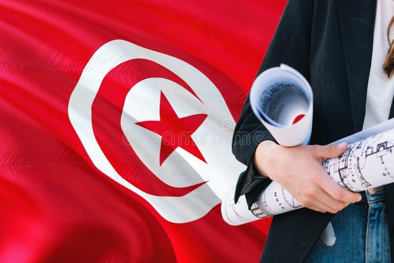 Tunesischer Architektenfrauen-Holdingplan gegen wellenartig bewegenden Flaggenhintergrund Tunesiens Bau- und Architekturkonzept lizenzfreie stockfotografie