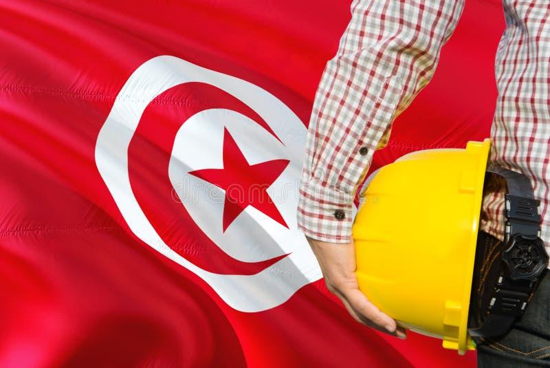 Tunezyjski inżynier trzyma żółtego zbawczego hełm z machać Tunezja chorągwianego tło Budowy i budynku poj?cie obrazy royalty free