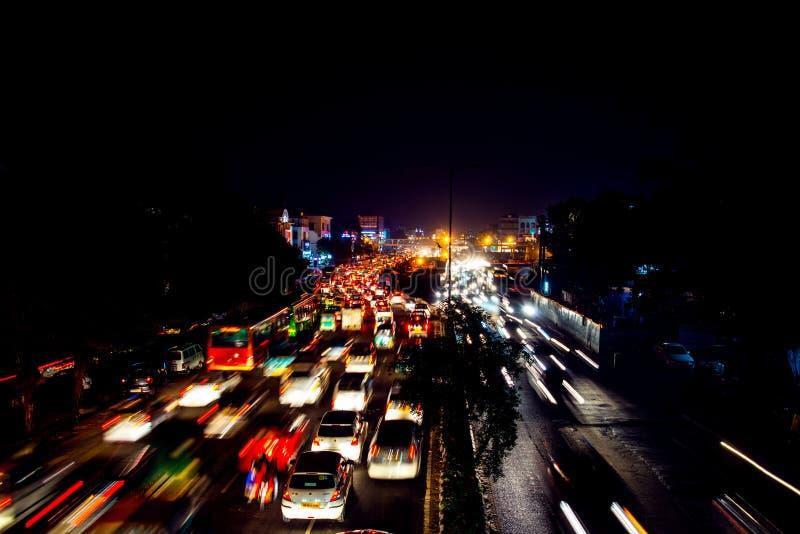 Tung biltrafik i centret av Delhi, Indien på natten royaltyfri bild