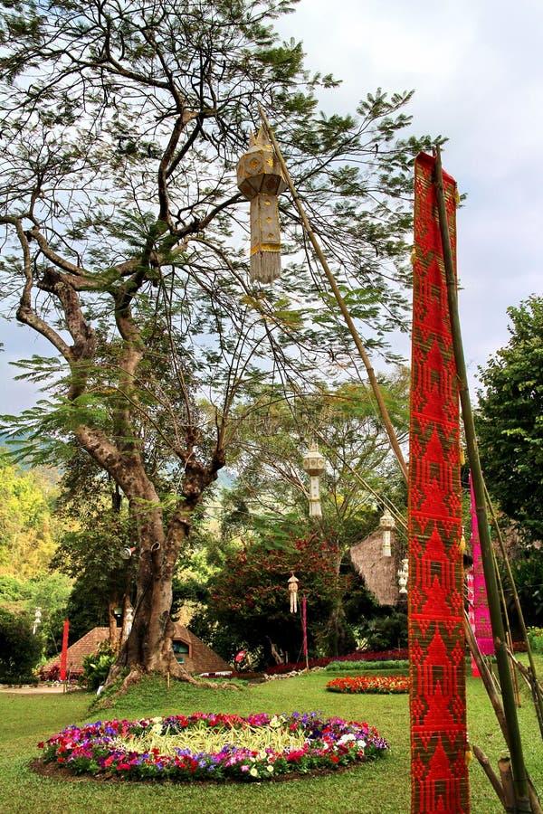 Tung flagga med det stora regnträdet och dekorerade blommor arkivbild