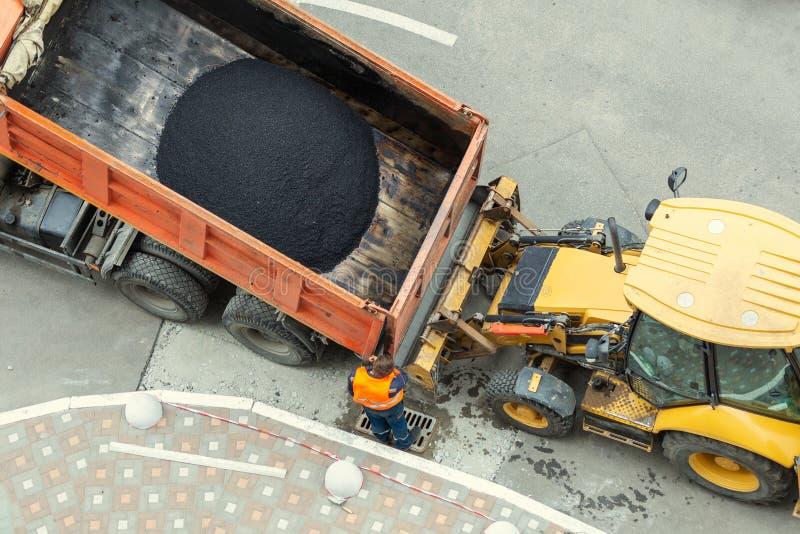 Tung industriell dumper som lastar av varm asfalt Stadsvägkonstruktion och förnyandeplats royaltyfri foto