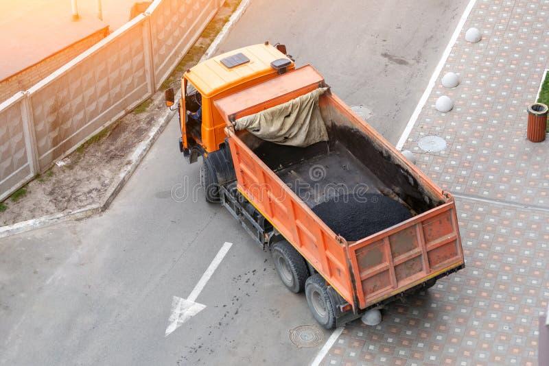 Tung industriell dumper som lastar av varm asfalt Stadsvägkonstruktion och förnyandeplats royaltyfria foton