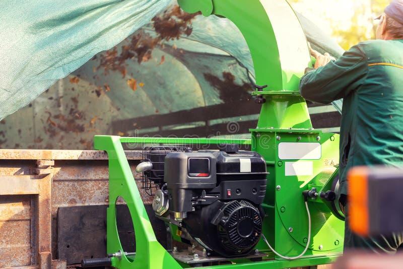 Tung industriell vaccuumladdare som laddar stupade sidor och skräp in i lastbilkropp Kommunal service som gör ren för att parkera arkivfoton