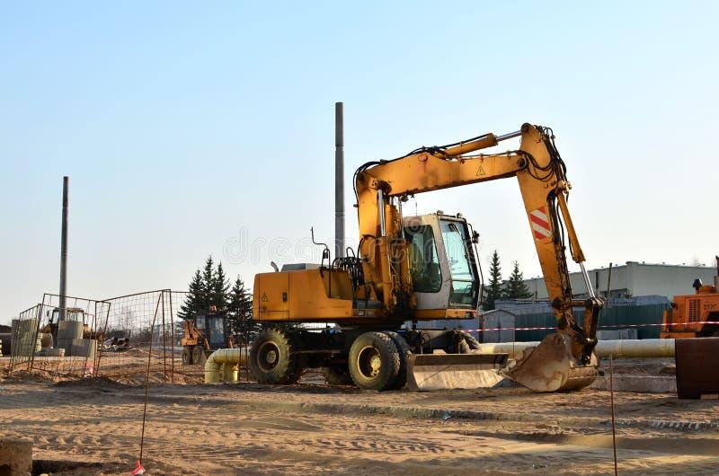 Tung konstruktionsutrustning och earthmoving grävskopor som arbetar på en konstruktionsplats i staden arkivfoton