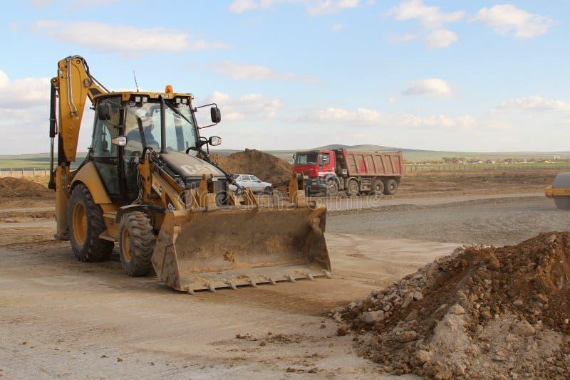 Tung konstruktionsutrustning som arbetar på en landningsbana som delen av utbyggnadsplanen för internationell flygplats för Donau arkivfoton