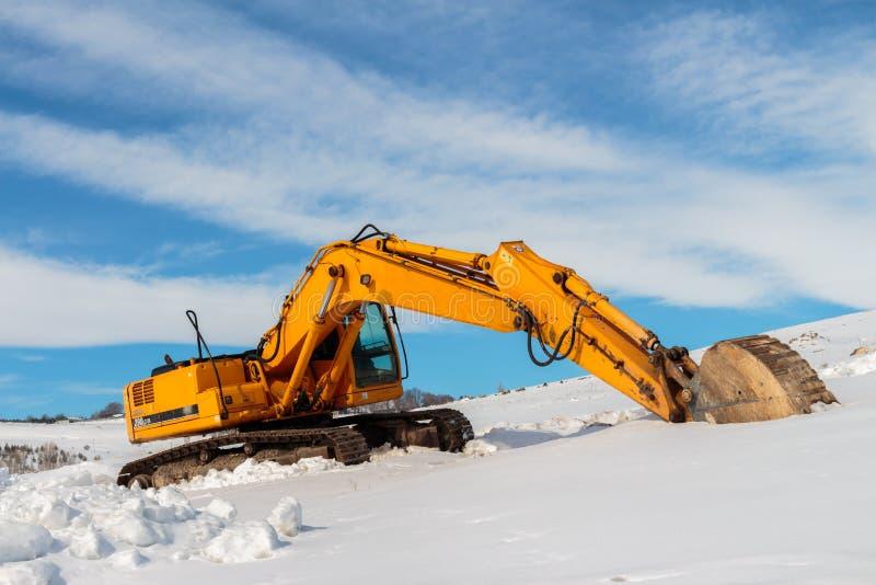 Tung konstruktionsutrustning som parkeras på den arbetsplatsen och vintern arkivbild
