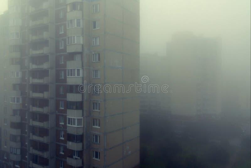 Tung morgondimma och avdunstning i staden med höghus royaltyfri bild